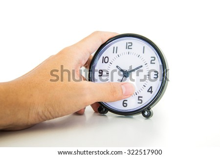 Hand holding alarm clock trying to wake up - stock photo
