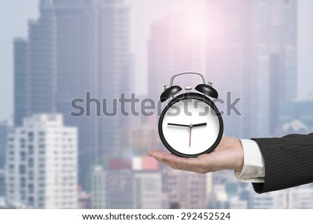 Hand holding alarm clock with sunlight city background. - stock photo