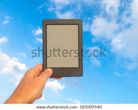 Hand holding an e-book reader  - stock photo