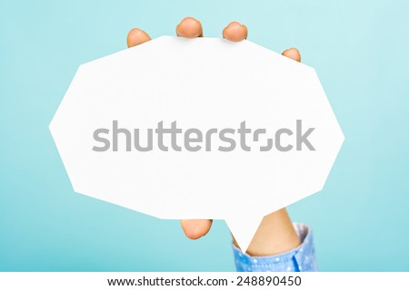 Hand holding an empty white speech bubble with straight cutting shape on blue background. - stock photo
