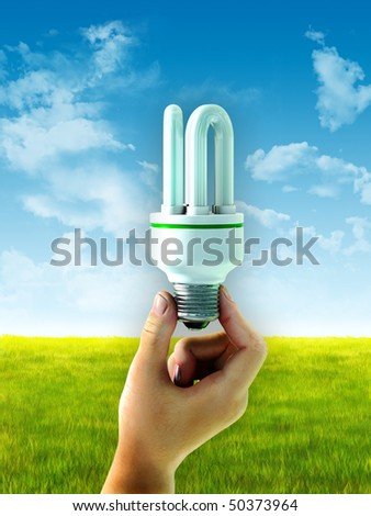 Hand holding an energy saving bulb over a summer landscape. Digital illustration. - stock photo