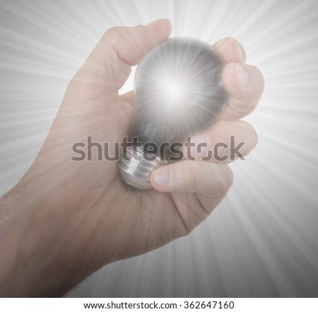Hand holding an light bulb isolated on white background - stock photo