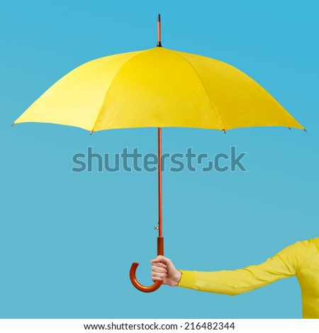 Hand holding an umbrella against a blue backgroud - stock photo