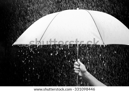 Hand holding an umbrella in rain black background business and fashion concept