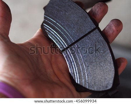 hand holding an uneven surface of a worn out disk brake pad in deep lines after use for a while but still thick and useable after rubbing and smoothing the surface again with sand paper