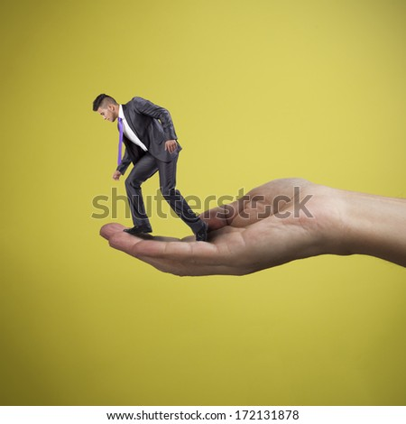 Hand holding and helping a young businessman - stock photo