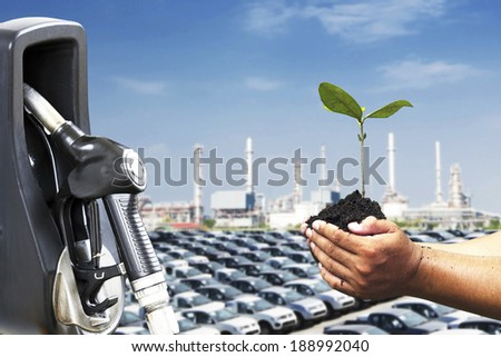 Hand holding and planting new tree to balance between nature and industry  - stock photo