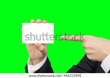 Hand holding and pointing blank business card for copyspace isolated on green background with clipping path - stock photo