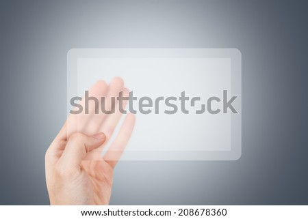 Hand holding and showing transparent technology tablet on dark background.