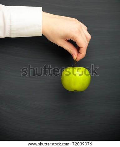 hand holding apple against blackboard background - stock photo