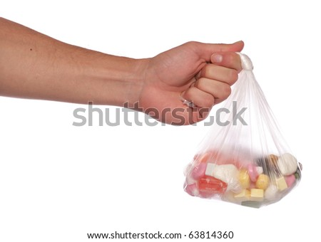 Hand holding bag of sweets studio cutout