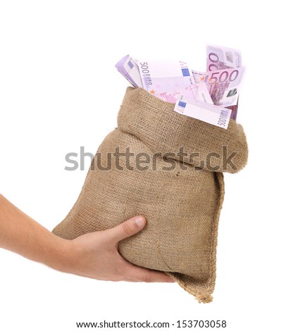 Hand holding bag with many banknotes - stock photo