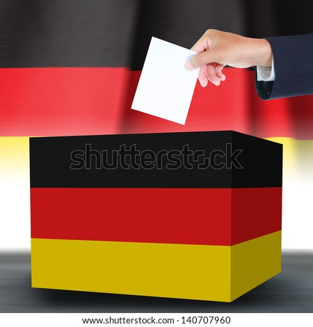 Hand holding ballot and box with the Germany flag in the background - stock photo