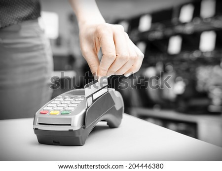 Hand holding  bank terminal and plastic card - stock photo