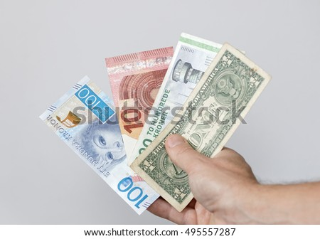 Hand holding banknotes from different countries, gray background. 100 SEK from sweden, 10 EUR from the european union, 200 DKR from denmark and 1 dollar from USA