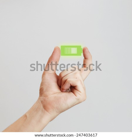 Hand holding battery icon, Male hand holding green battery  - power concept