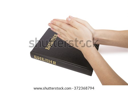 Hand holding bible on white background.