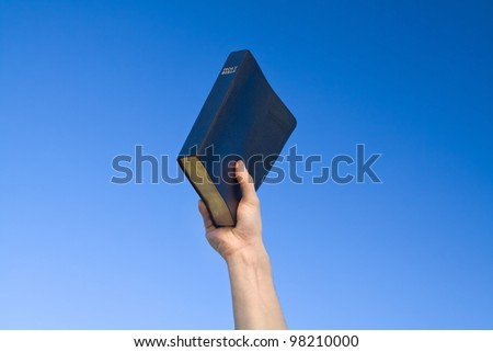 Hand holding Bible over blue sky - stock photo