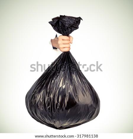 Hand holding black bag of rubbish.  Studio shot. - stock photo