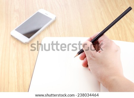Hand holding black pencil and writing on blank open notebook with smartphone beside it on wooden table,Template mock up for adding your text - stock photo