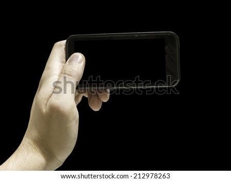 Hand holding Black Smartphone in horizontal on black background