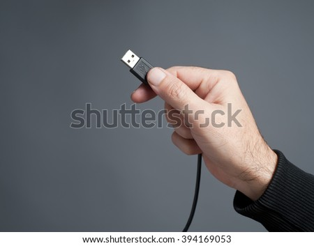 Hand holding black USB cable