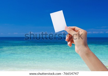 Hand Holding Blank Card, tropical beach as background - stock photo
