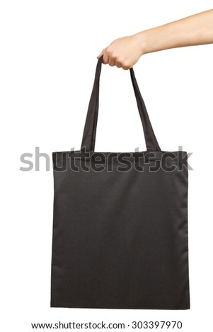 Hand holding blank fabric tote bag isolated on white - stock photo