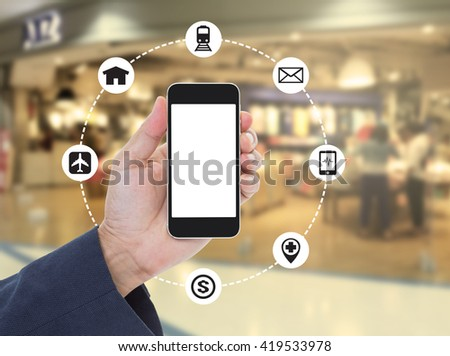 Hand holding blank screen mobile phone on blurred shopping mall background - stock photo