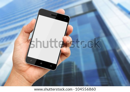 Hand holding blank screen smart phone with buiding background - stock photo