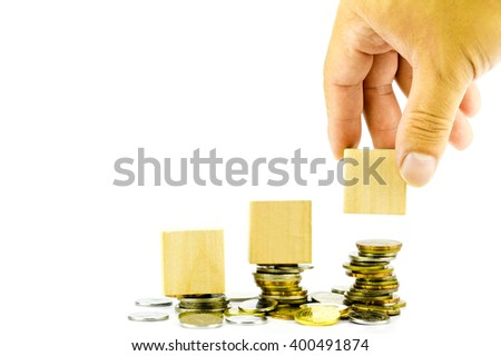 Hand holding blank wooden block with stacked coins - stock photo