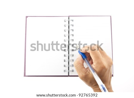 Hand holding blue pen over notebook - stock photo