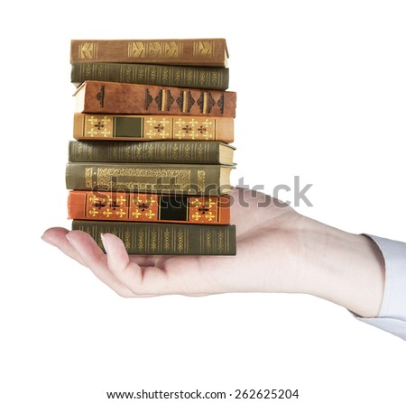 Hand holding book pile isolated on white background. Education concept - stock photo