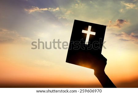 Hand holding book with cross on sunset background - stock photo