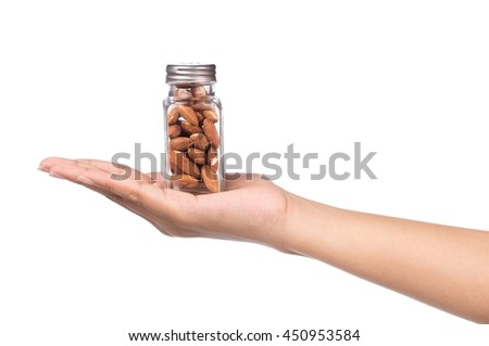hand holding bottle of Almonds isolated on white background