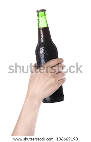 hand holding Bottle of dark beer with drops isolated on a white background - stock photo