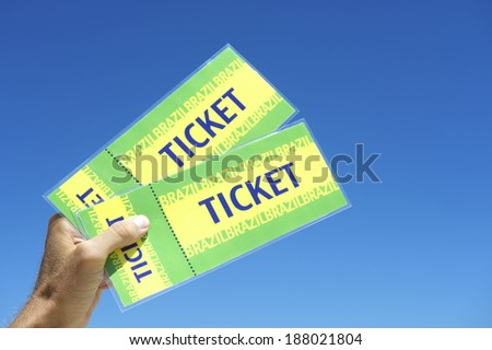 Hand holding Brazil tickets in bright blue tropical sky