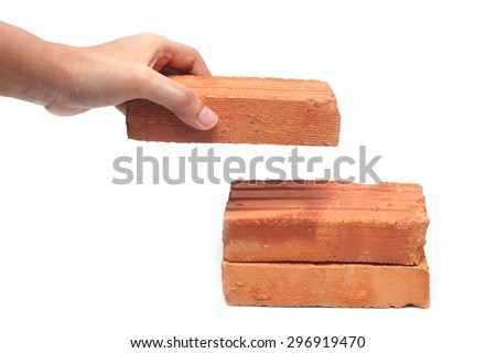 Hand holding brick construction on white