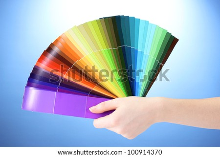 hand holding bright palette of colors on blue background