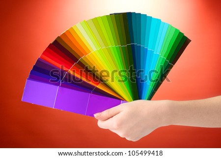 hand holding bright palette of colors on red background