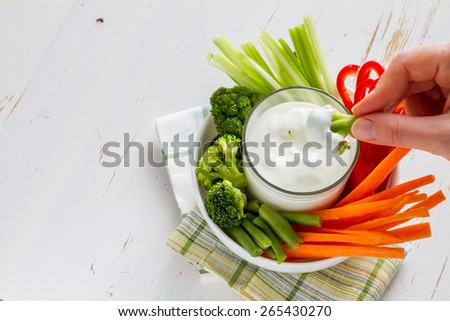 Hand holding broccoli, white bowl with carrot, celery, pepper, broccoli and green beans, yogurt sauce, white wood background - stock photo