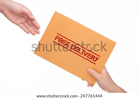 Hand holding Brown envelope with free delivery stamp. woman's hand passes the envelope male hand - stock photo