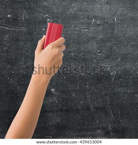 Hand holding brush erase on black chalkboard - stock photo