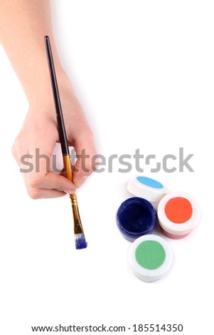 Hand holding brush with paints isolated on white - stock photo