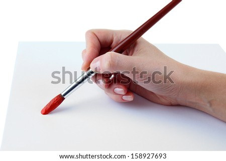 Hand holding brush with red paint isolated on white