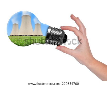 Hand holding bulb with nuclear power plant  isolated on white  - stock photo