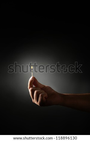 Hand holding burning match against dark background. - stock photo