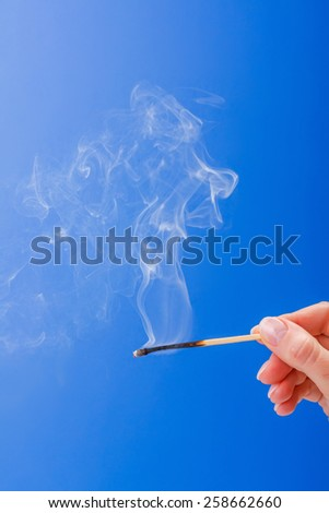 Hand holding burnt fuming matchstick on blue background - stock photo