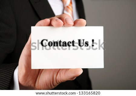 hand holding business card with the message contact us