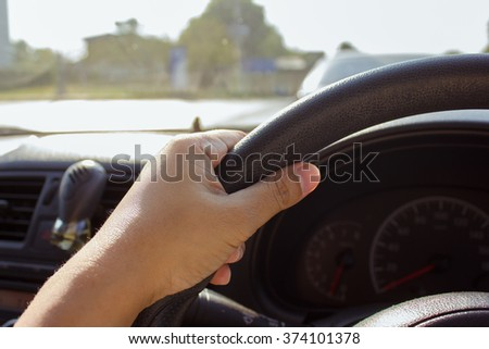 hand holding car control wheel